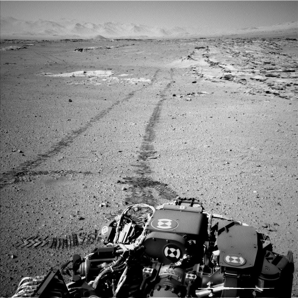 "NASA's Curiosity Mars rover used its Navigation Camera (Navcam) for this look back after finishing a long drive on Feb. 19, 2014. The rows of rocks just to the right of the fresh wheel tracks in this view are an outcrop called ""Junda."" This view is looking toward the east-northeast."