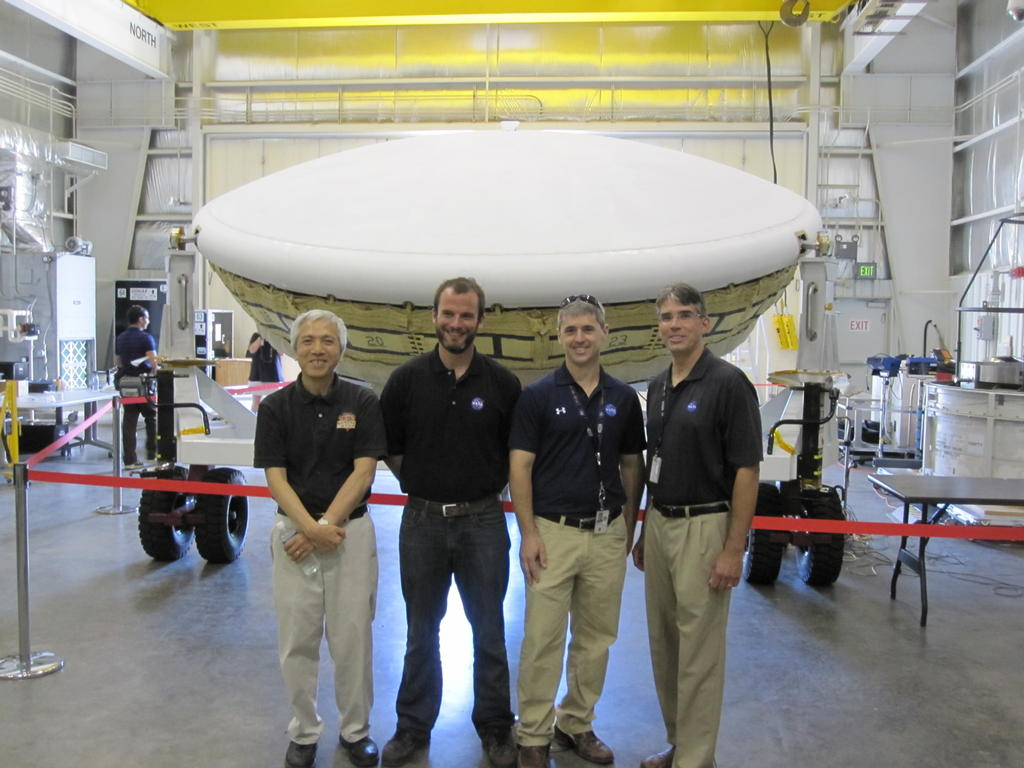 Members of the team for NASA's Low-Density Supersonic Decelerator (LDSD) stand in front of the project's saucer-shaped test vehicle at the U.S. Navy's Pacific Missile Range Facility in Kauai, Hawaii.