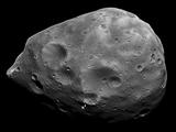 Visible in great detail is Phobos' irregular shape, strangely dark terrain, numerous unusual grooves, and a spectacular chain of craters crossing the image center.