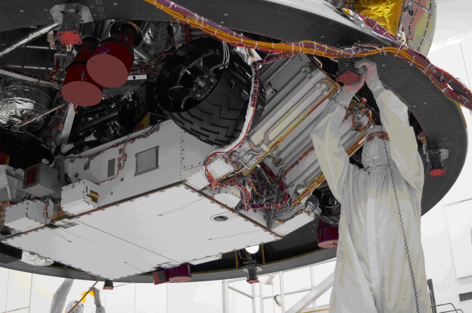 This image shows an engineer dressed in 'clean room' coveralls, working on the rover which is over head.