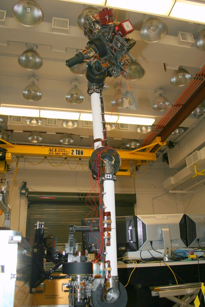 In the middle of this image, the long robotic arm rises straight up toward the ceiling of the lab where it is being tested. The arm is white, and is flexible at several gray round 'joints.' Red wires dangle and are strung along various parts of the arm. At the end of the arm is a complicated set of instruments. In the background, a yellow crane for lifting equipment up to 2 tons (4,000 pounds) can slide along the ceiling to place heavy equipment anywhere in the room. A metal garage-like door and computer stations lie behind the area where the arm is extended.