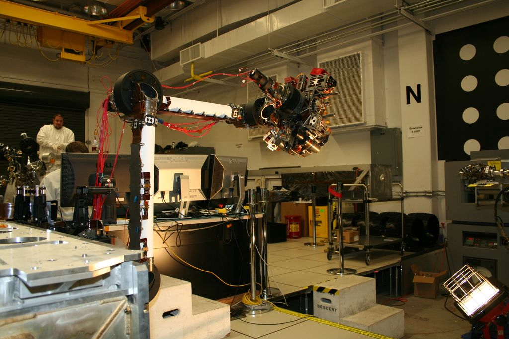 In the middle of this picture, the robotic arm is bent at nearly a 90-degree angle, with the instruments on the end of the arm reaching to the right. Behind the arm is the laboratory where it is being tested. One engineer is hidden behind a bank of computers, while another with a goatee stands watching in the back, beneath a yellow ceiling crane. Both engineers wear white lab coats. Metal lab equipment is scattered throughout the room.