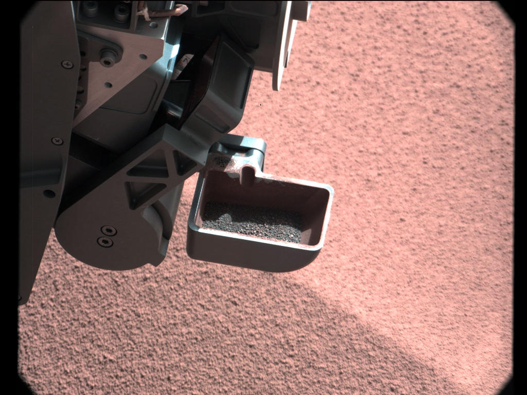 In this image, the scoop on NASA's Curiosity rover shows the larger soil particles that were too big to filter through a sample-processing sieve that is porous only to particles less than 0.006 inches (150 microns) across.
