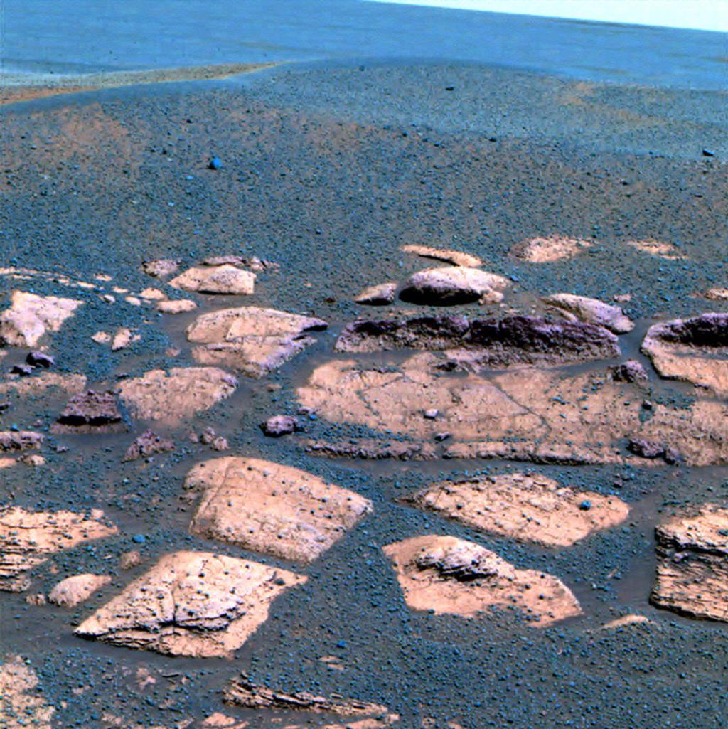 """Esta imagem falsa cor sugere que as planícies além da pequena cratera onde a Mars Exploration Rover Opportunity agora se senta estão cheios com o mesmo material cinza escuro encontrados dentro da cratera na forma de esférulas ou """"blueberries""""."""