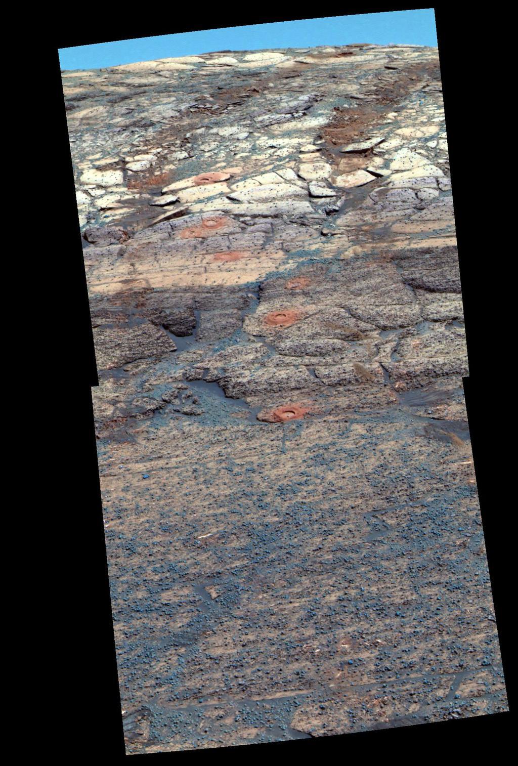 """Este ponto de vista da câmera panorâmica do Mars Exploration Rover Opportunity é uma rendição composta de cores falsas dos primeiros sete buracos que ferramenta de rocha abrasão do rover escavadas na encosta interior da """"cratera Endurance""""."""