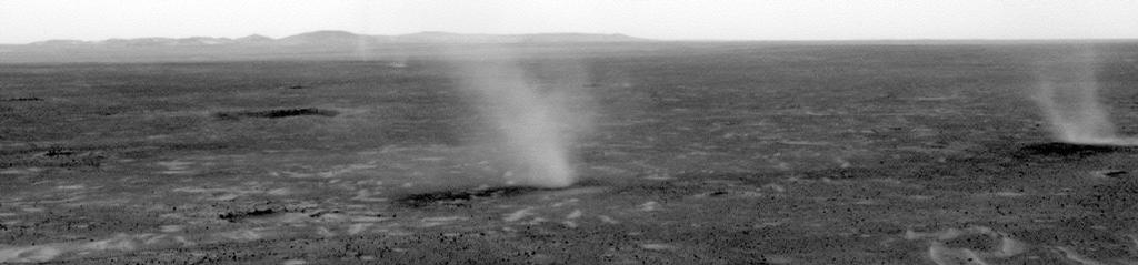 This image hows several dust devils moving from right to left across a plain inside Mars' Gusev Crater, as seen from the vantage point of NASA's Mars Exploration Rover Spirit in hills rising from the plain.