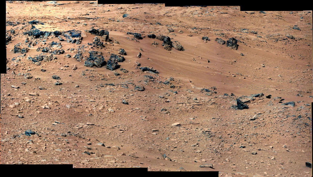 "This patch of windblown sand and dust downhill from a cluster of dark rocks is the ""Rocknest"" site, which has been selected as the likely location for first use of the scoop on the arm of NASA's Mars rover Curiosity."