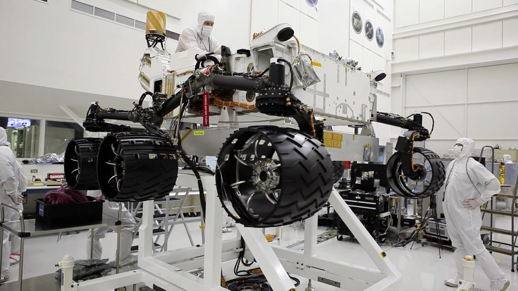 "This image was taken in the clean room where the Curiosity rover is being assembled. It shows the rover, which is about the size of an SUV, hoisted on a white lift, with its black wheels suspended in the air. One engineer is on top of the hoist and is leaning over the rover body, while another is looking up on the ground floor to the right of the rover. Both engineers are wearing white ""bunny suits"" to keep them from contaminating any equipment."