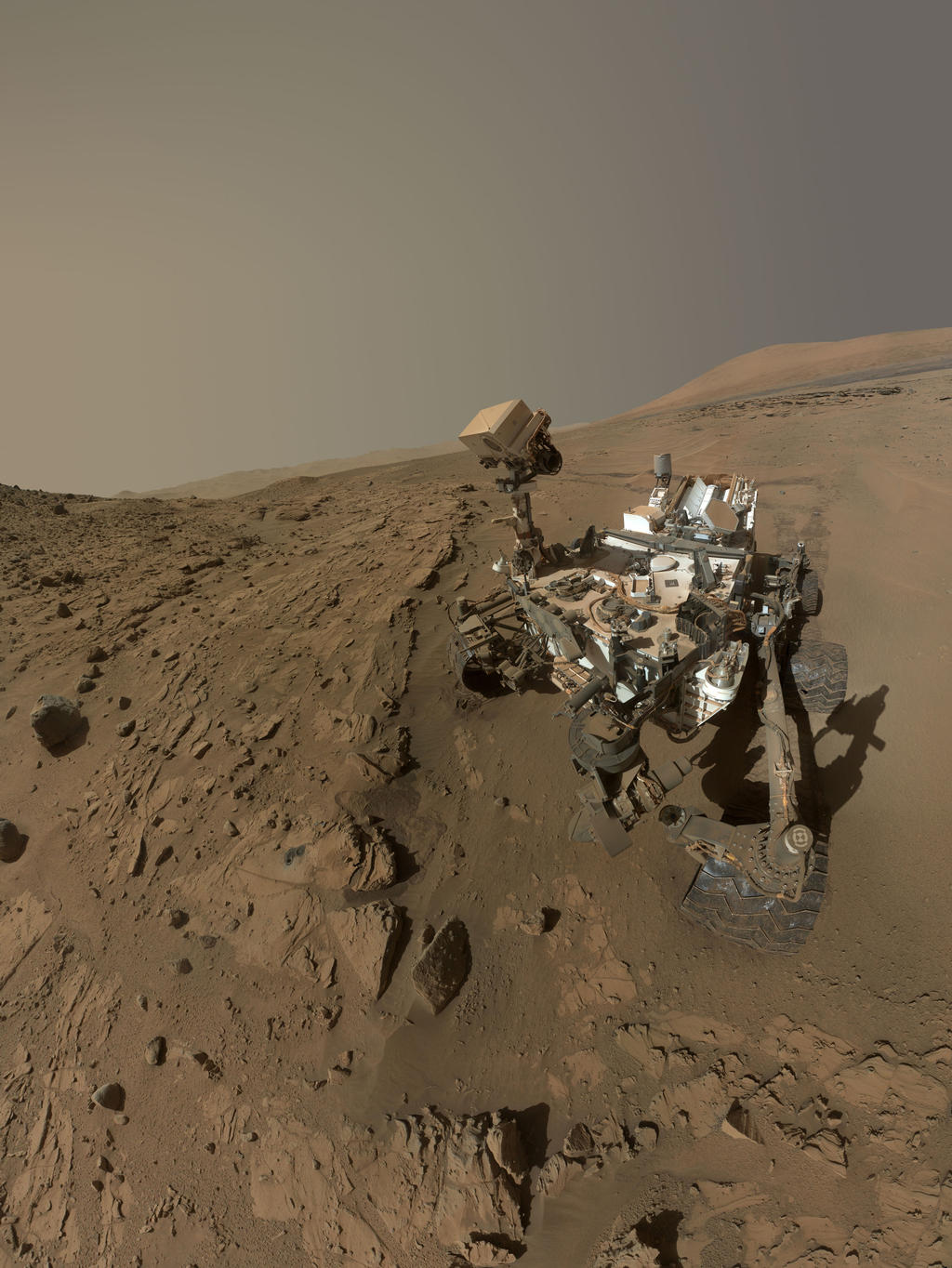 Curiosity, rover, self-portrait, rock, drilling, windjana, waypoint, kimberley - This image is a self-portrait of the Curiosity rover taken from the site with the rover's 'head' down, with rock formations surrounding it and Mount Sharp in the background.