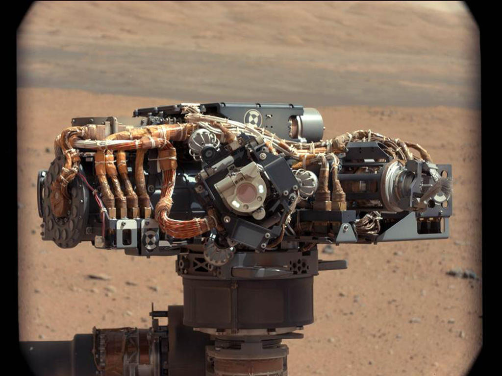 This image shows the Mars Hand Lens Imager (MAHLI) on NASA's Curiosity rover, with the Martian landscape in the background.