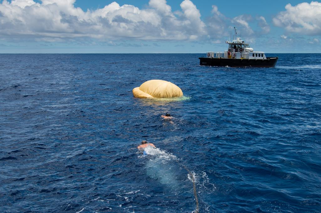 Hours after the June 28, 2014, test of NASA's Low-Density Supersonic Decelerator over the U.S. Navy's Pacific Missile Range, two members of the Navy's Explosive Ordinance Disposal swim towards the pilot ballute that was used to deploy the parachute. In the background, the recovery vessel Mana'o II.