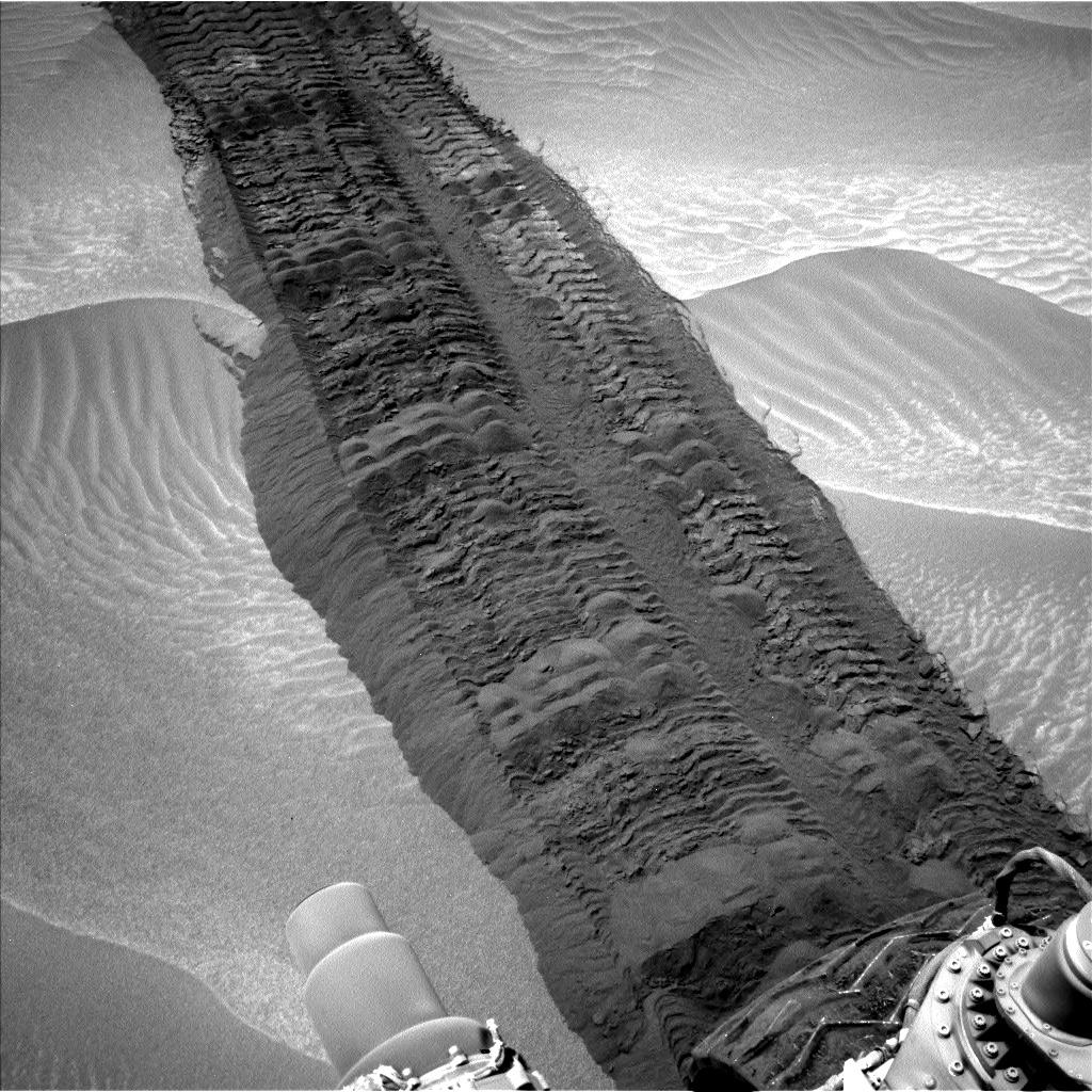 "This image from the Navigation Camera on NASA's Curiosity Mars rover shows wheel tracks printed by the rover as it drove on the sandy floor of a lowland called ""Hidden Valley"" on the route toward Mount Sharp."