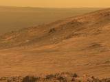 "This view from NASA's Opportunity Mars rover shows part of ""Marathon Valley,"" a destination on the western rim of Endeavour Crater, as seen from an overlook north of the valley. It was taken by the rover's Pancam on March 13, 2015. This version is in approximate true color."