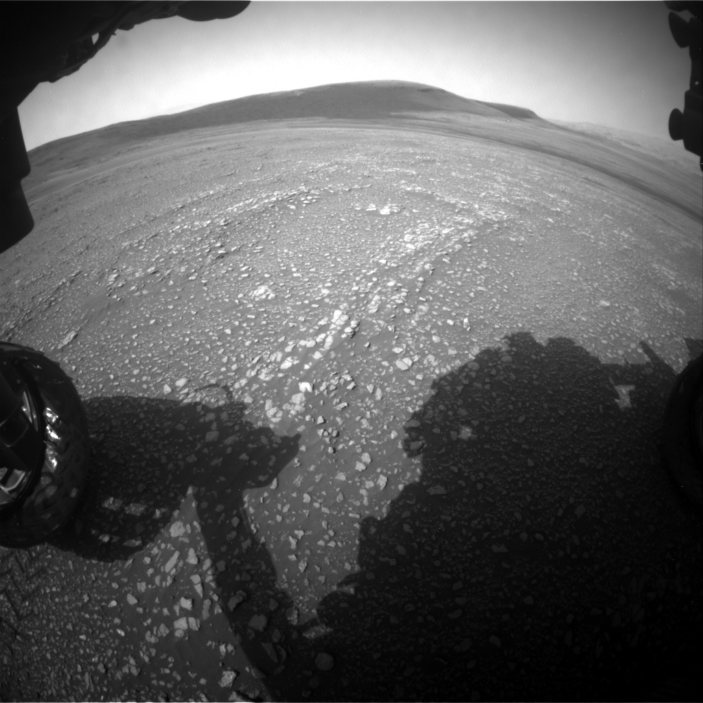 Image taken by the Mars rover Curiosity with a hill in the background and shadow of the rover's front-left wheel taken by its Front Hazcam.