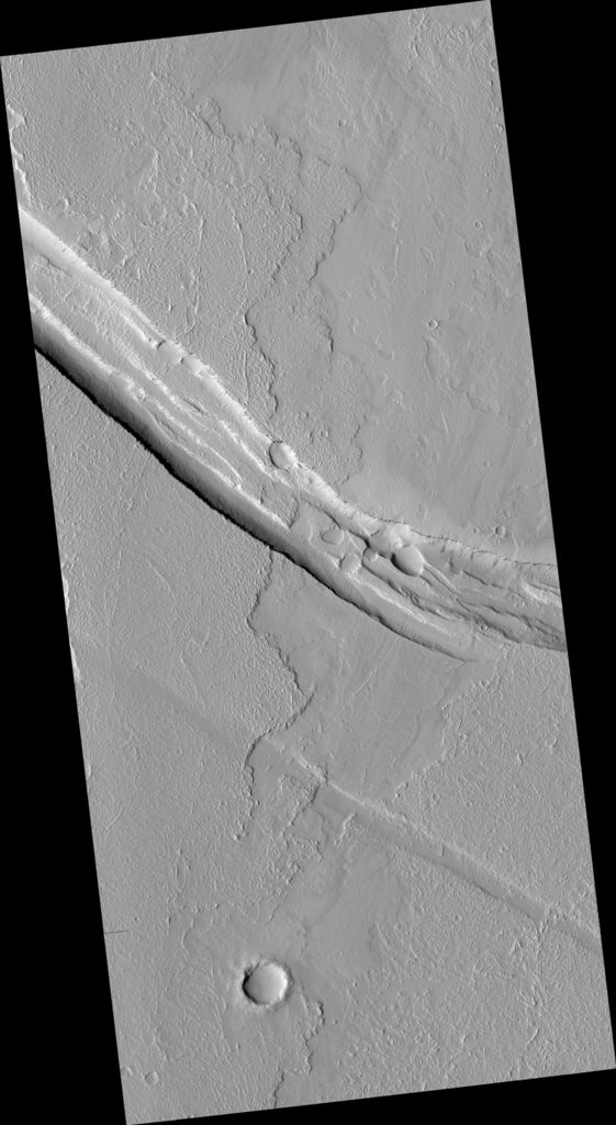 This image shows a graben (a trough formed when the ground drops between two parallel faults) and a lava flow in the Tharsis volcanic province of Mars. North is up.