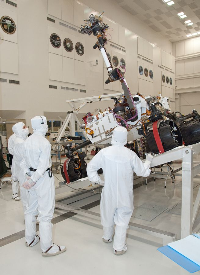 NASA's next Mars rover, Curiosity, stretches its robotic arm upward during Sept. 3, 2010, tests on a tilt table in a clean room at NASA's Jet Propulsion Labotatory, Pasadena, Calif. Test operators in clean room garb monitor the motions simulating maneuvers that the rover might make while on a sloped surface on Mars.