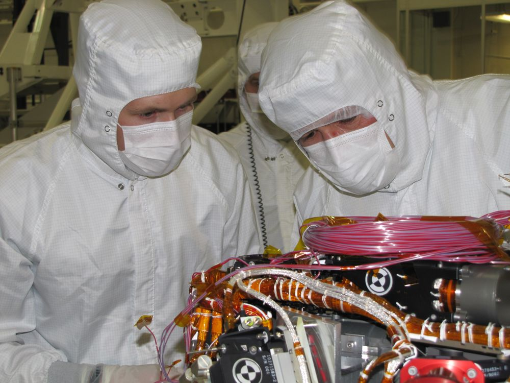 Grad student Nicholas Boyd (left) and Principal Investigator Ralf Gellert, both of the University of Guelph, Ontario, Canada, prepare for the installation of the Alpha Particle X-ray Spectrometer sensor head during testing at NASA's Jet Propulsion Laboratory.