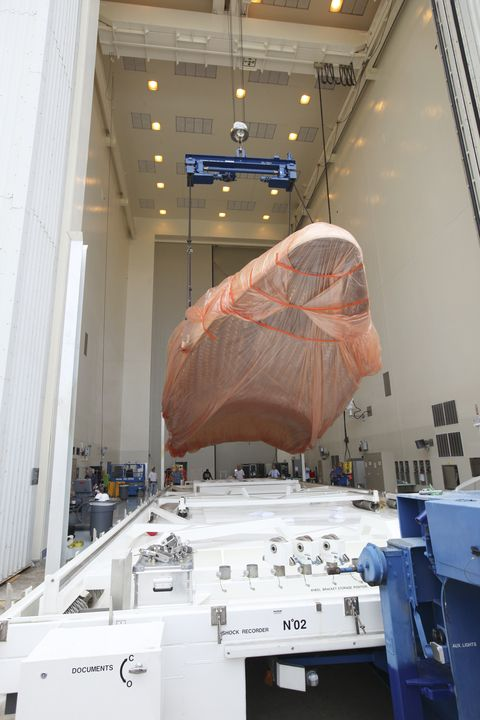 Half of the Atlas V payload fairing for NASA's Mars Science Laboratory (MSL) mission, encased in plastic, is lifted from its transportation pallet in the airlock of the Payload Hazardous Servicing Facility at NASA's Kennedy Space Center in Florida.