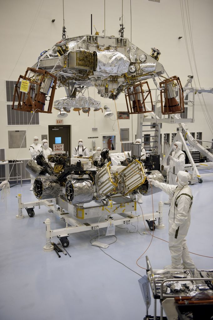 Under the watchful eyes of technicians at the Payload Hazardous Servicing Facility at NASA's Kennedy Space Center in Florida, an overhead crane lowers a rocket-powered descent stage over NASA's Mars Science Laboratory (MSL) rover, known as Curiosity, for integration.