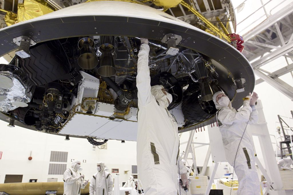 In the Payload Hazardous Servicing Facility at NASA's Kennedy Space Center in Florida, technicians work beneath NASA's Mars Science Laboratory (MSL) mission aeroshell, (containing the compact car-sized rover Curiosity), which has been mated to the cruise stage.