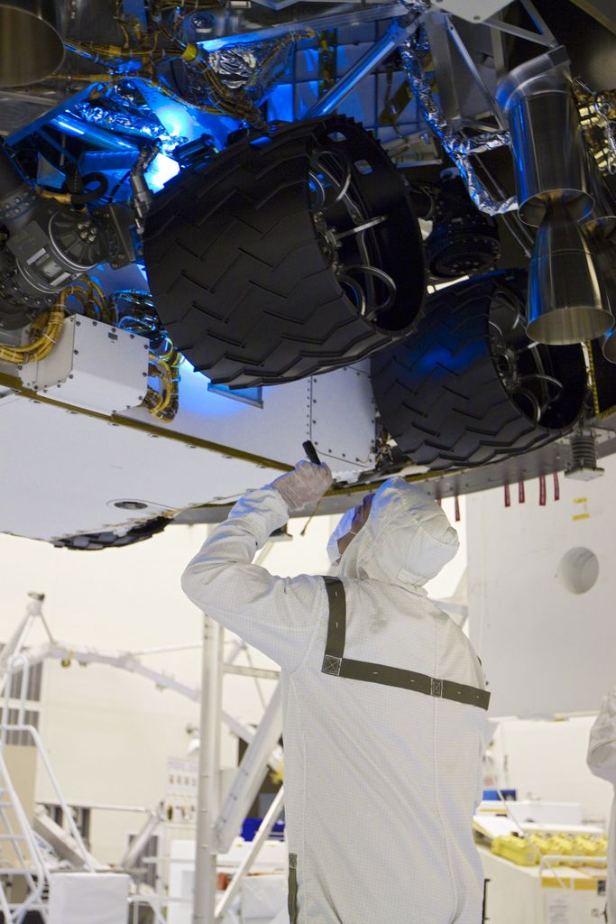 In the Payload Hazardous Servicing Facility at NASA's Kennedy Space Center in Florida, a technician inspects beneath NASA's Mars Science Laboratory (MSL) mission aeroshell, (containing the compact car-sized rover Curiosity), which has been mated to the cruise stage.