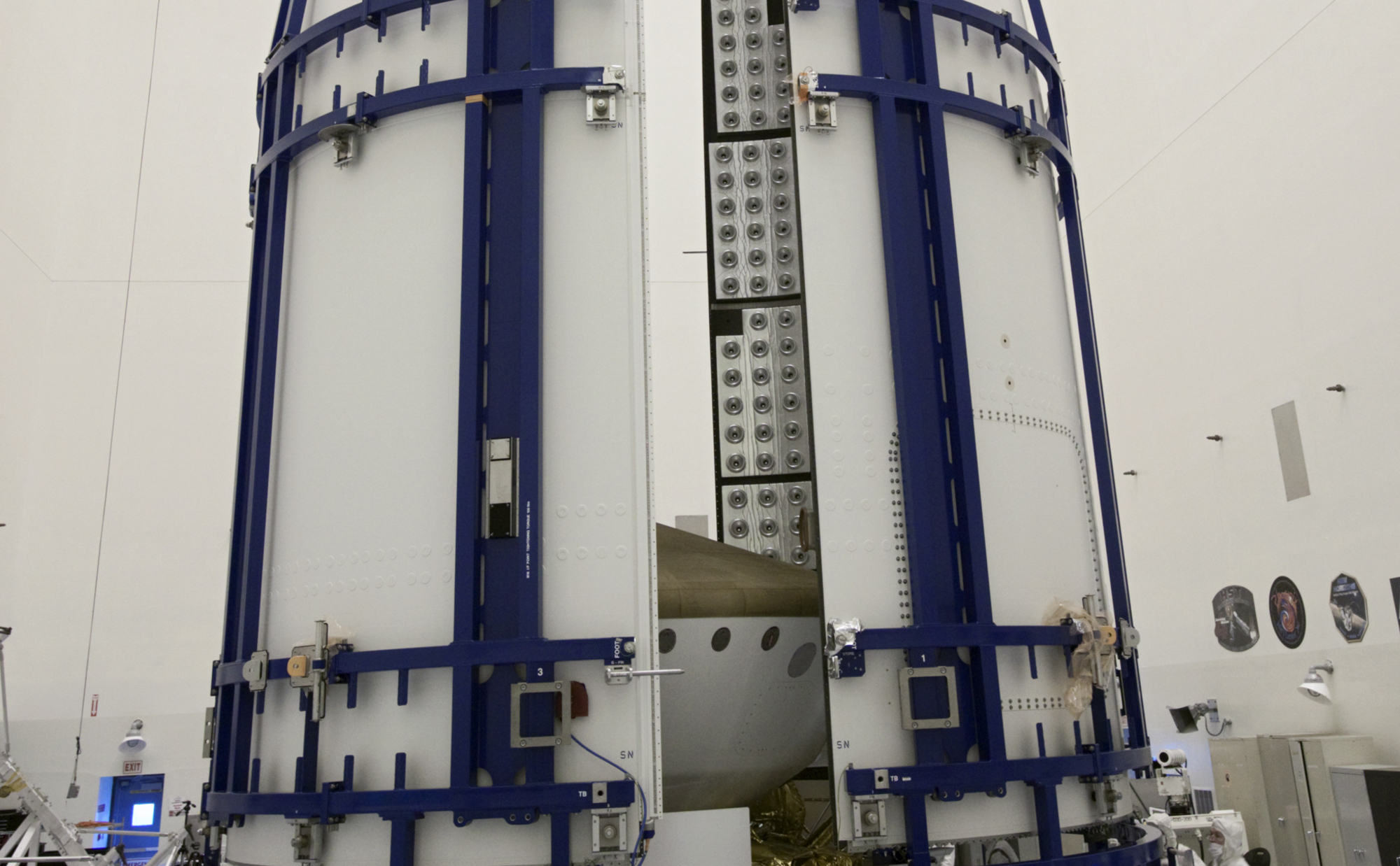 In the Payload Hazardous Servicing Facility at NASA's Kennedy Space Center in Florida, sections of an Atlas V rocket payload fairing obscure NASA's Mars Science Laboratory (MSL) from view as they close in around it.