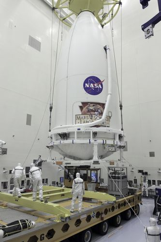 In the Payload Hazardous Servicing Facility at NASA's Kennedy Space Center in Florida, technicians assist as the payload fairing of an Atlas V rocket approaches a transporter for the move to Space Launch Complex 41.