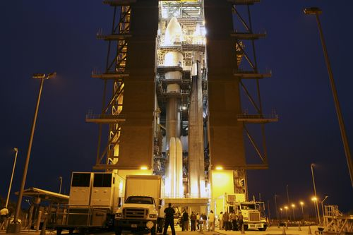 The Atlas V rocket set to launch NASA's Mars Science Laboratory (MSL) mission is illuminated inside the Vertical Integration Facility at Space Launch Complex 41, where employees have gathered to hoist the spacecraft's multi-mission radioisotope thermoelectric generator (MMRTG).