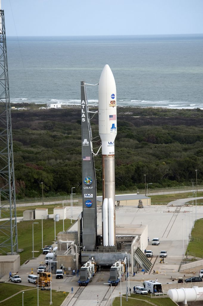 On Cape Canaveral Air Force Station in Florida, the 197-foot-tall United Launch Alliance Atlas V rocket arrives on the launch pad at Space Launch Complex-41, situated near the Atlantic Ocean.