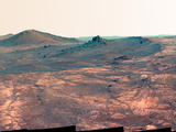 "An elongated crater called ""Spirit of St. Louis,"" with a rock spire in it, dominates this scene from the panoramic camera (Pancam) on NASA's Mars Exploration Rover Opportunity."