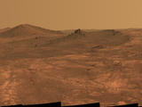 "An elongated crater called ""Spirit of St. Louis,"" with a rock spire in it, dominates a recent scene from the panoramic camera (Pancam) on NASA's Mars Exploration Rover Opportunity."