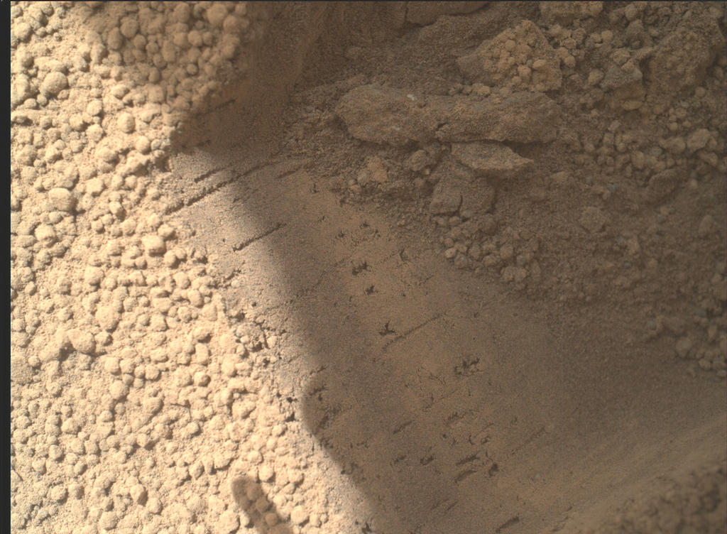 This image contributed to an interpretation by NASA's Mars rover Curiosity science team that some of the bright particles on the ground near the rover are native Martian material.