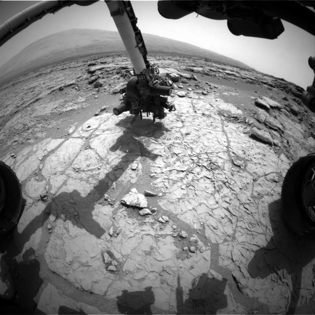 The percussion drill in the turret of tools at the end of the robotic arm of NASA's Mars rover Curiosity has been positioned in contact with the rock surface in this image from the rover's front Hazard-Avoidance Camera (Hazcam).