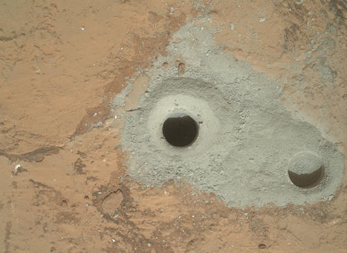 "At the center of this image from NASA's Curiosity rover is the hole in a rock called ""John Klein"" where the rover conducted its first sample drilling on Mars."