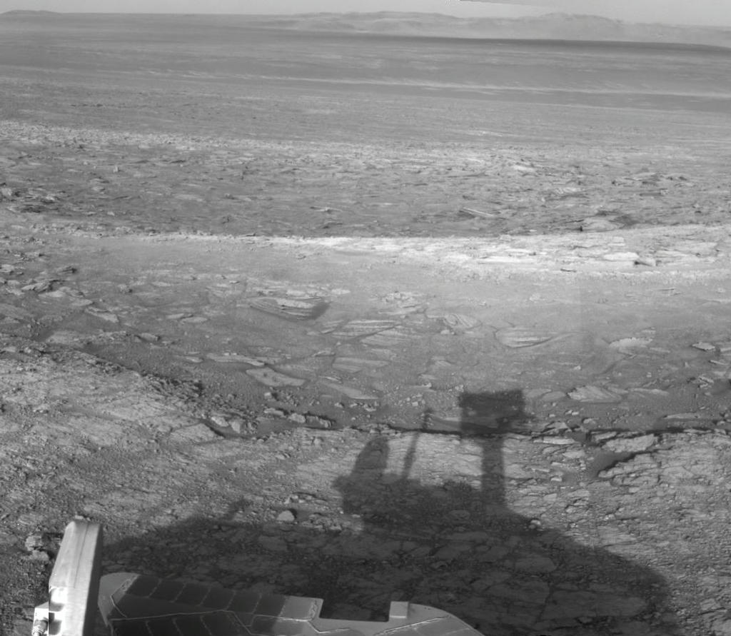 NASA's Mars Exploration Rover Opportunity used its navigation camera to record this vista looking eastward across Endeavour Crater, with the rover's own shadow in the foreground.
