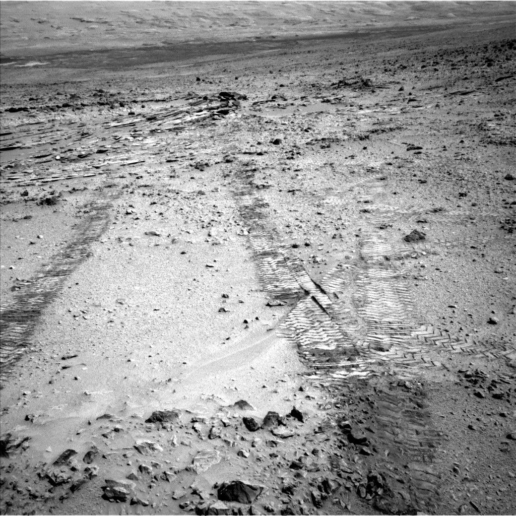 "This view from the left Navigation Camera (Navcam) of NASA's Mars Rover Curiosity looks back at wheel tracks made during the first drive away from the last science target in the ""Glenelg"" area."