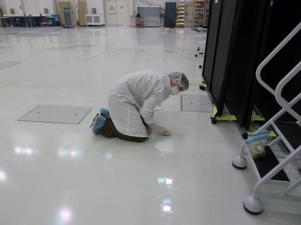 A microbiologist collects a swab sample from the floor of a spacecraft assembly clean room at NASA's Jet Propulsion Laboratory.