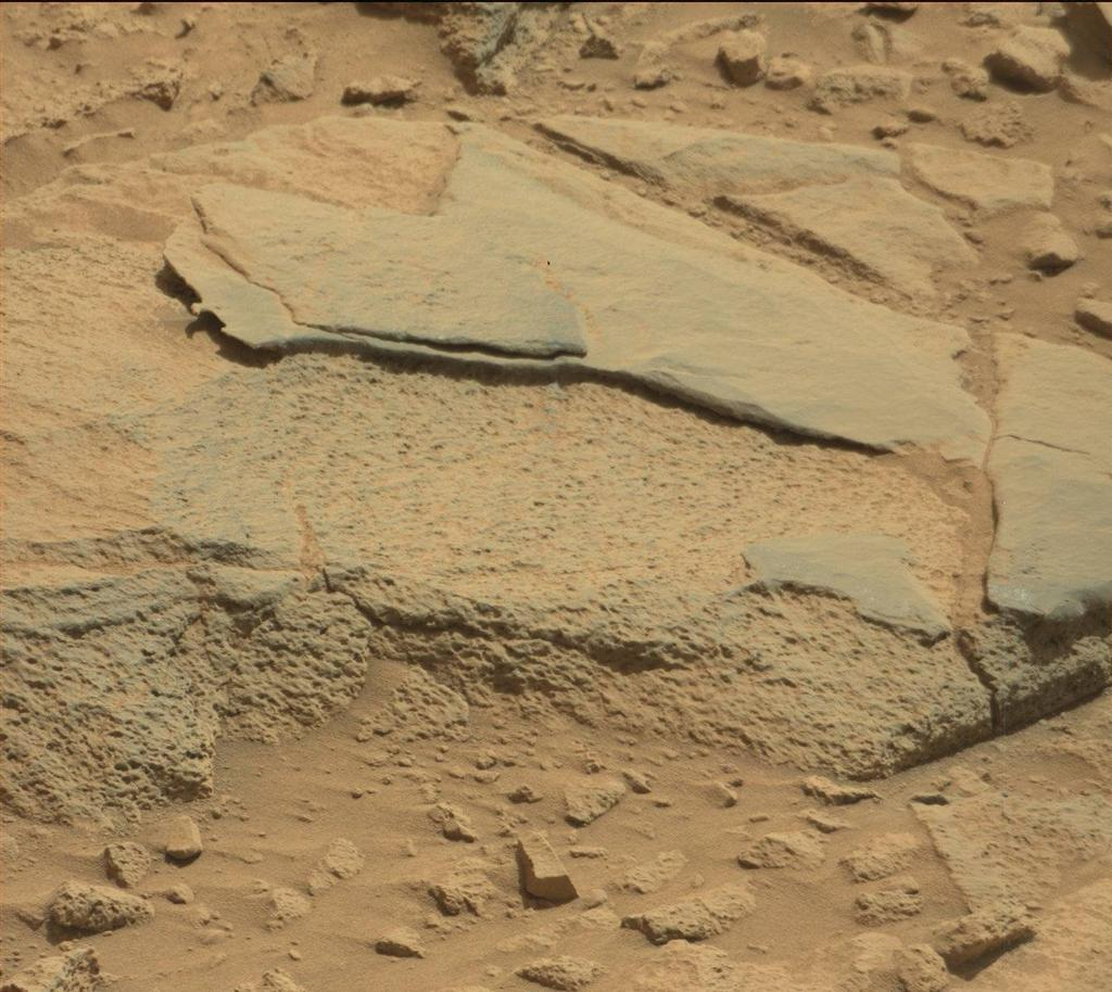 "The rock ""Ithaca"" shown here, with a rougher lower texture and smoother texture on top, appears to be a piece of the local sedimentary bedrock protruding from the surrounding soil in Gale Crater."