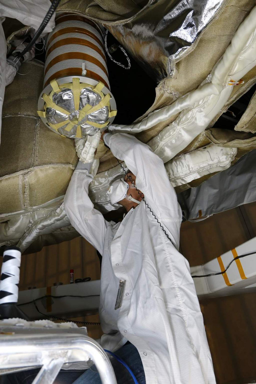 An engineer works on the Parachute Deployment Device of the Low Density Supersonic Decelerator test vehicle in this image taken at the Missile Assembly Building at the US Navy's Pacific Missile Range Facility in Kaua'i, Hawaii.