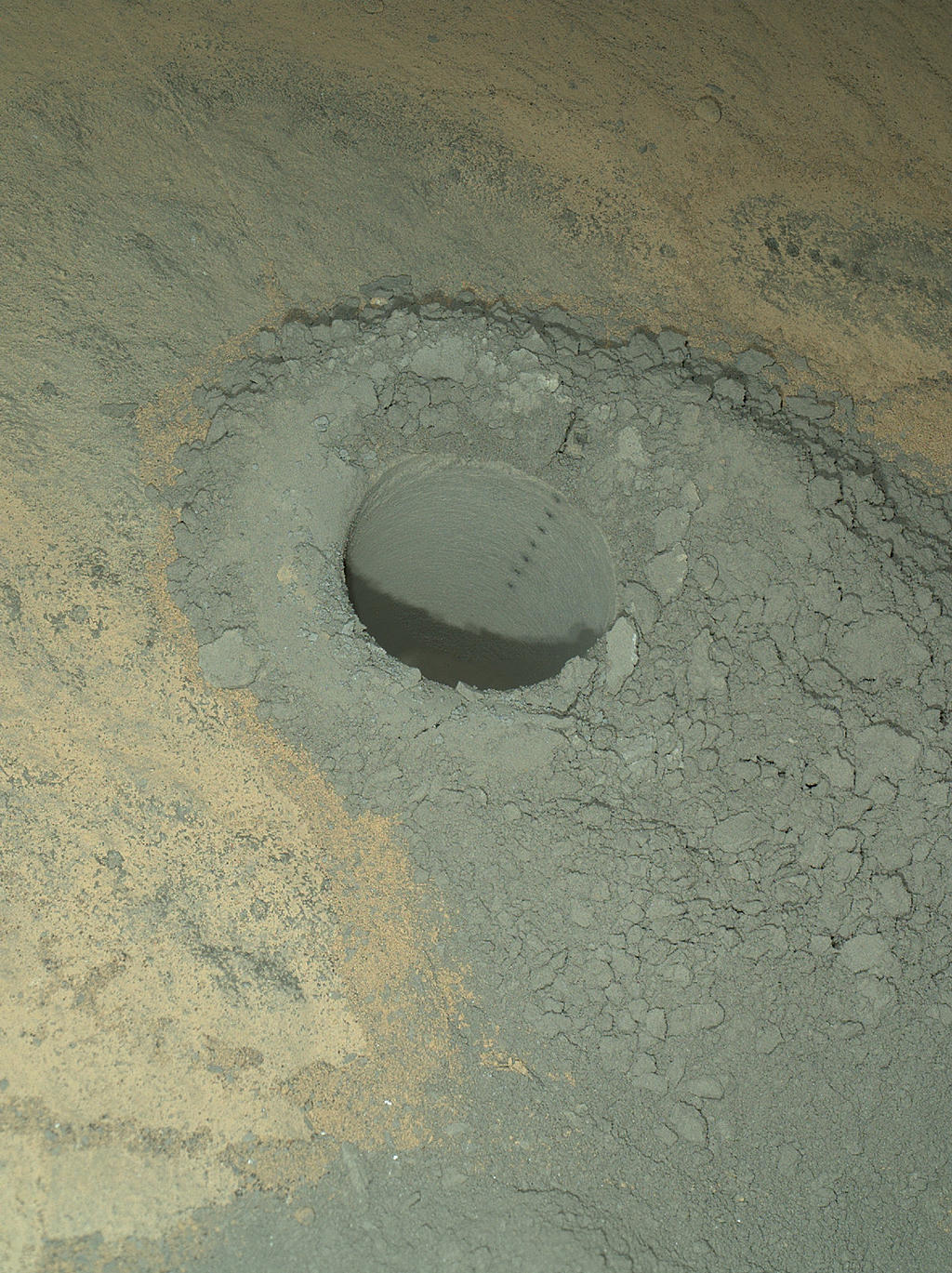 The Mars Hand Lens Imager on NASA's Curiosity Mars rover provided this nighttime view of a hole produced by the rover's drill and, inside the hole, a line of scars produced by the rover's rock-zapping laser. The camera used its own white-light LEDs to illuminate the scene on May 13, 2014.