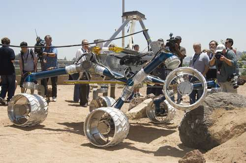 In this image, about a dozen people watch the large Scarecrow rover drive over a grayish orange boulder in an outdoor sandbox. Scarecrow is about the size of a small compact car. Its 'legs,' (mobility system) are a vibrant blue color and its large wheels are silver and covered in chevron-like cleats. Members of the media hold cameras.