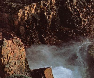 This image shows a white, frothy stream flowing down a canyon between tall, red, volcanic cliffs.