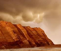 This image shows layered, red cliffs rising up from a flat, brown surface. The cliff surface slants from right to left, with the nearest cliffs on the right-hand side of the image and those farther away toward the left. Pinkish-tan clouds hover above the crests of the cliffs.
