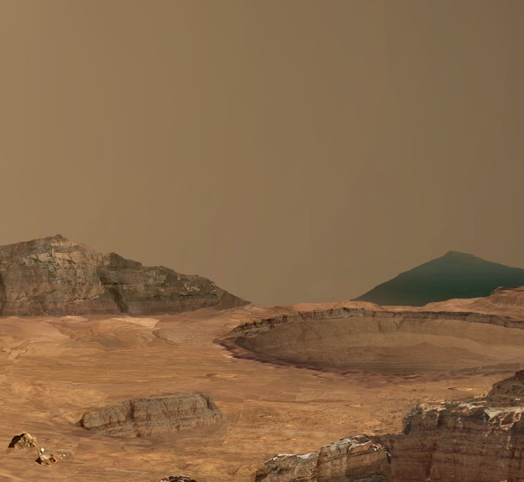 This image shows a round crater exposing horizontal layers in its walls. Around it is an undulating brown surface. In both the foreground, in the lower right corner of the image, and in the backround, forming the horizon, are cliffs exposing horizontal layers of rock. The sky is a typical shade of martian peachy pink.