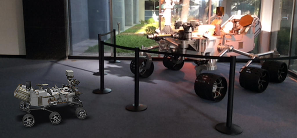 A 3D, augmented reality model of NASA's Curiosity rover shares a scene with a real life model of the rover in a view taken with NASA's Spacecraft 3D app.