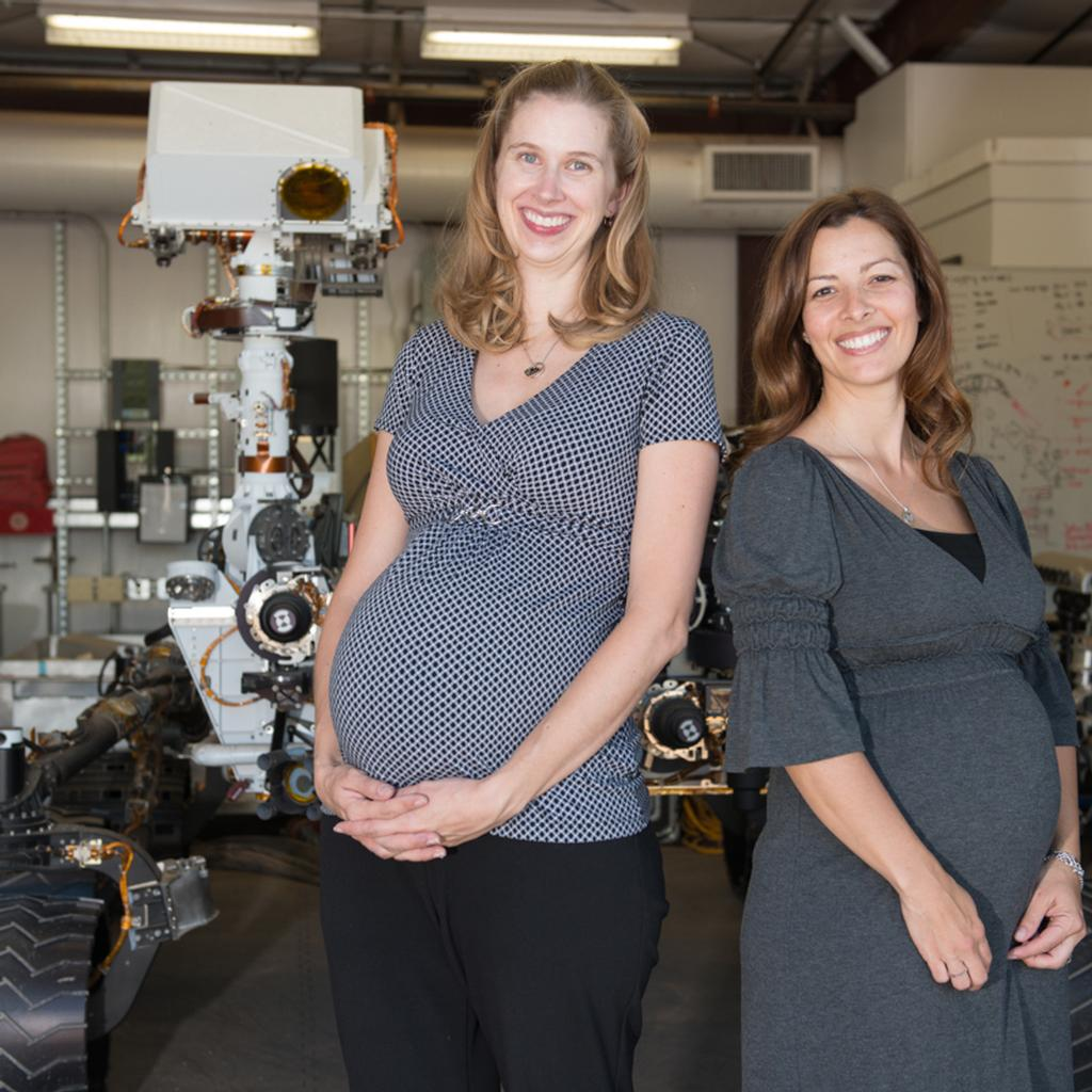 "Emily Eelkema Stough, Tactical Uplink Lead and Jessica Samuels, Engineering Operations Team Chief, pose for the cameras in the ""Mars Yard"" with Curiosity's ground test model in the background."