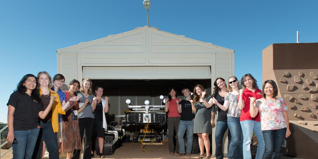 "This is a picture of some of the women working on the Curiosity rover posing with Curiosity's mobility double, ""Scarecrow,"" used to test drive under different soil conditions in the JPL ""Mars Yard."""