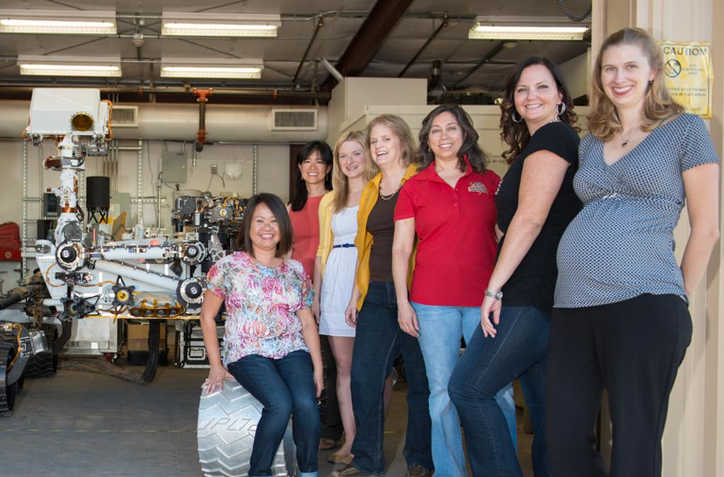 "Pictured here are a few of the women working on Mars with the Curiosity test rover model in the background. The image was taken in the ""Mars Yard"" where the ground test model of the Curiosity rover is housed."