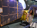 The full-scale mock-up of NASA's MarCO CubeSat held by Farah Alibay, a systems engineer at NASA's Jet Propulsion Laboratory, is dwarfed by the one-half-scale model of NASA's Mars Reconnaissance Orbiter behind her.