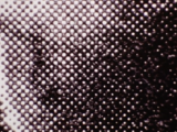 This image seems like a random series of light and dark grey dots when viewed up close. When seen from farther away the dots blend together to make an image of a tennis ball.